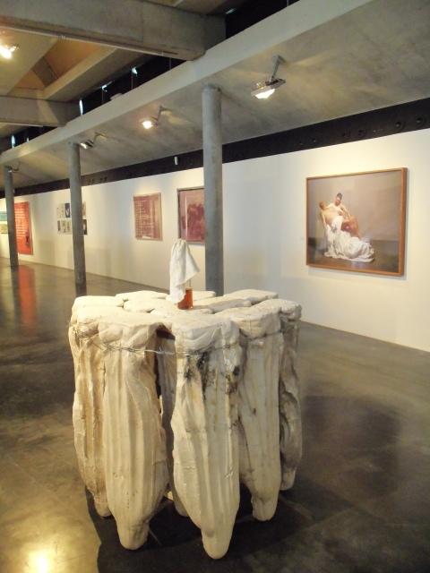 Ausstellungsansicht, im Vordergrund Madonnenskulptur von Eduard Winklhofer, Senza titolo, 2006, Gips-Madonnen, Stacheldraht, Molotowcocktail